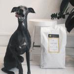 Zwarte windhond die haar bek aflikt bij het zien van de grote zak hondenvoeding van BuddyBites