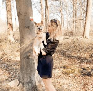 Baasje met haar Shiba Inu hond in haar armen die samen in het bos staan.