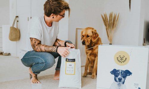 hond kijkt benieuwd naar zak buddybites die baasje opent